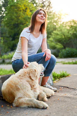 Cheerful girl looking up on walk with retriever on summer
