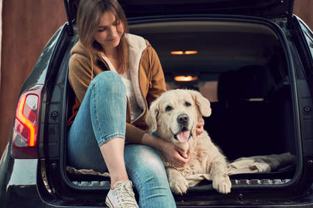 Smiling woman with golden retriever sit in open trunk of black car