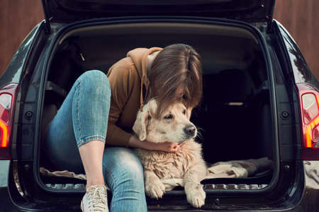 Young woman hugs golden retriever while sitting in open trunk of black car
