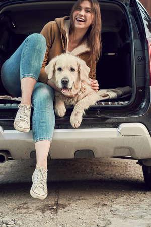 Happy woman hugs golden retriever sitting in open trunk of black car