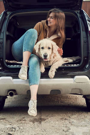 Happy woman looking at side while hugging golden retriever in open trunk of black car. 版權商用圖片