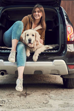 Happy woman looking at camera while hugging golden retriever in open trunk of black car.
