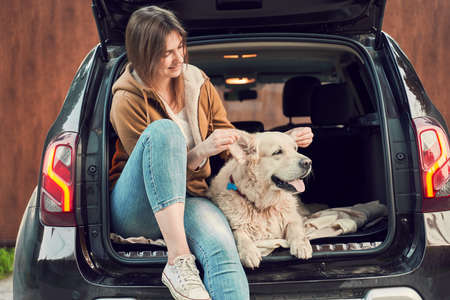 Woman with dog sitting in open trunk of black car