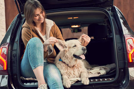Smiling woman with dog sitting in open trunk of black car
