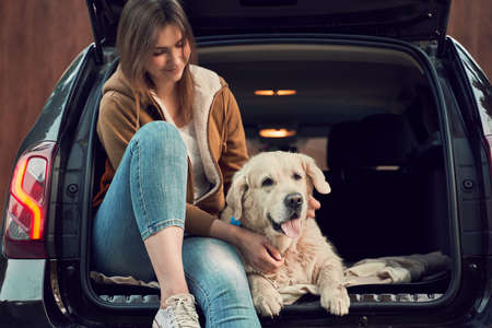 Young woman with golden retriever sit in open trunk of black car