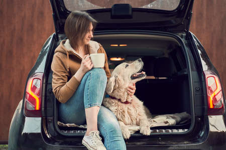 Happy girl with mug in hand with dog sitting in open trunk of black car. 版權商用圖片