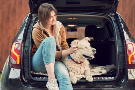 Young woman with dog sitting in open trunk of black car