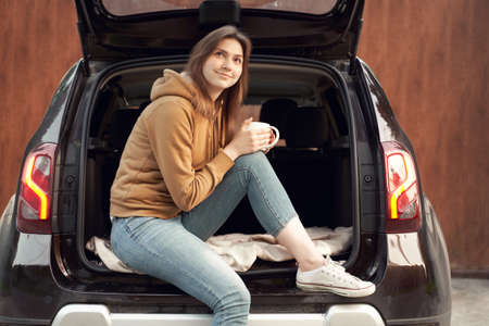 Young brunette with mug sitting in open trunk of black car on summer day