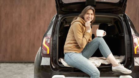 Happy brunette with mug sitting in open trunk of black car on summer day