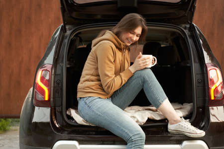 Smiling brunette with mug sitting in open trunk of black car on summer day