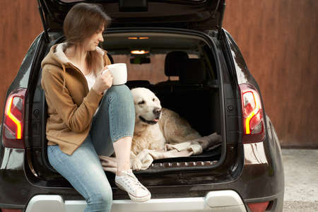 Young woman with mug in hand with dog sitting in open trunk of black car