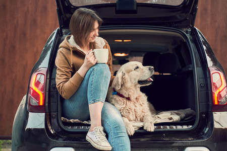 Young girl with mug in hand with dog sitting in open trunk of black car