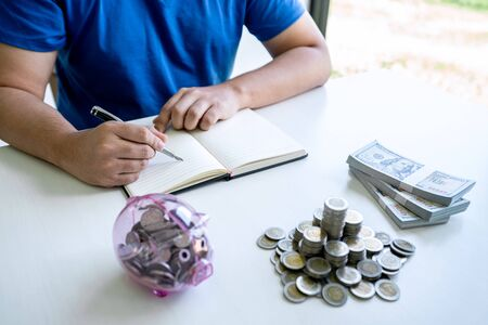 Man putting coins to planning growing saving to strategy with piggy bank for future plan fund of travel , education, home and retirement.