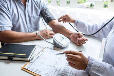 Doctor using stethoscope checking measuring arterial blood pressure on arm to a patient in the hospital.