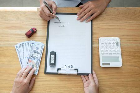 Concepto de seguro y alquiler de automóvil, joven vendedor que recibe dinero y entrega la llave del automóvil al cliente después de firmar el contrato de acuerdo con un buen trato aprobado para alquiler o compra.
