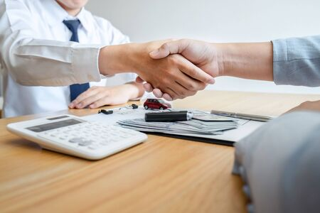 Car rental and Insurance concept, Young salesman shaking hands with customer after sign agreement contract with approved good deal for rent or purchase.