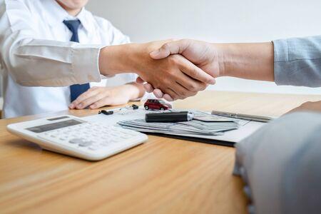 Concepto de seguro y alquiler de coches, joven vendedor dándose la mano con el cliente después de firmar el contrato de acuerdo con un buen trato aprobado para alquiler o compra.