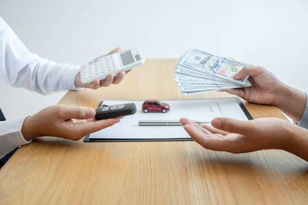 Concepto de seguro y alquiler de automóvil, joven vendedor que recibe dinero y entrega la llave del automóvil al cliente después de firmar el contrato de acuerdo con un buen trato aprobado para alquiler o compra. Foto de archivo