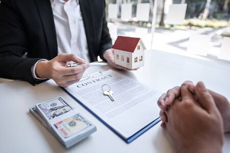 Real estate agent are presenting home loan and giving house, keys to customer after signing contract to buy house with approved property application form.