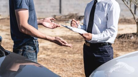 Insurance Agent and customer assessed negotiation, checking and signing on report claim form process after accident collision, Traffic Accident and insurance concept. Archivio Fotografico