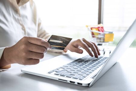 Business woman using laptop and holding credit card for paying detail page display online shopping purchase and entry security code to inputting card information. Stock fotó