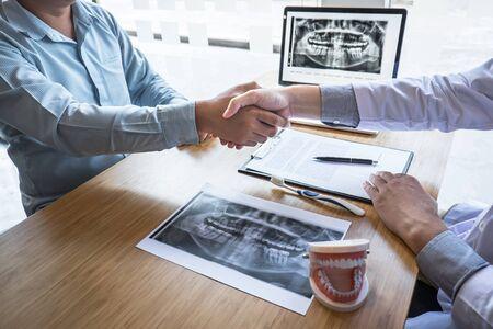 Professioneller Zahnarzt zeigt Kiefer und Zähne das Röntgenfoto und schüttelt Hände nach Abschluss der Diskussion während der Erklärung der Beratungsbehandlungsprobleme mit dem Patienten.