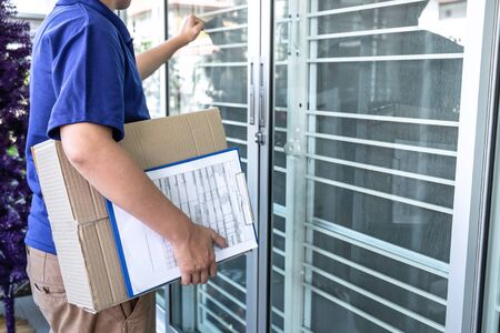 Delivery man deliver box parcel package and clipboard documents sending to customer in front of the house.