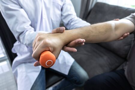 Doctor physiotherapist treating arm pain patient doing physical therapy exercises with his therapist in clinic - sport physical therapy concept.