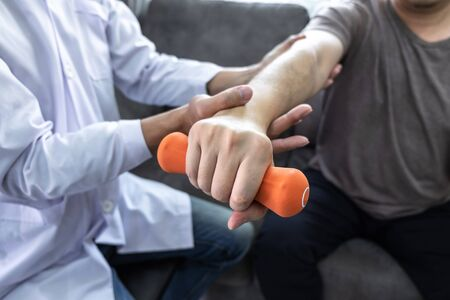 Doctor physiotherapist treating rehabilitation arm pain patient doing physical therapy exercises with his therapist treatment on stretching in clinic - sport physical therapy concept. Stockfoto