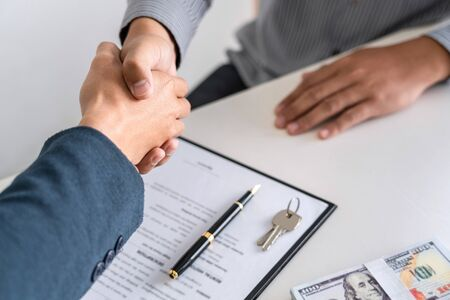 Real estate agent are shaking hands after good deal and giving house, keys to customer after signing contract to buy house with approved property application form. Фото со стока