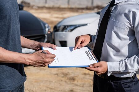 Insurance Agent examining car crash and customer assessed negotiation, checking and signing on report claim form process after accident collision, Accident and insurance concept.