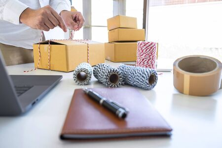 Young business owner work at home receive order customer and take note list with report and packing the product order delivery online to sending destination, Online business and delivery concept. Stock fotó