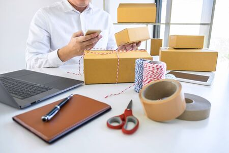 Young entrepreneur business owner work at home, small business startup receive order client and take note working with report and pack the product on purchase delivery online to sending destination.