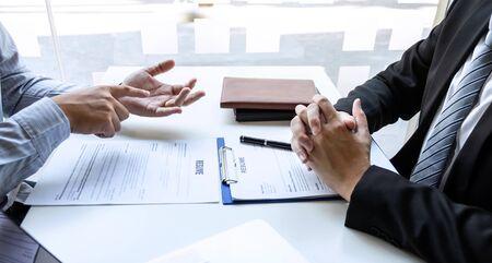 L'intervista dell'uomo d'affari considera una conversazione di ripresa durante il profilo del candidato di condurre un colloquio di lavoro ascolta le risposte mentre è seduto alla riunione di lavoro in ufficio. Archivio Fotografico