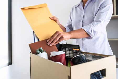 Images of stress of woman employee has a brown cardboard box and intend sending resignation letter to boss employer consider in order to contract for quit or layoff of job leaving from work.