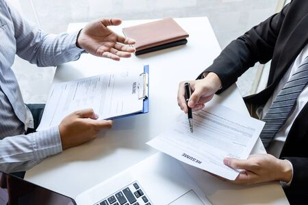 Businessman interview consider a resume conversation during about profile of candidate of conducting a job interview listen to answers while sitting at the working meeting in office. Banque d'images