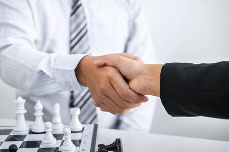 Black and White chess with player, Businessman and Businesswoman shaking hands after end game of thinking strategy to moving chess figure in competition with opposite player and planning.