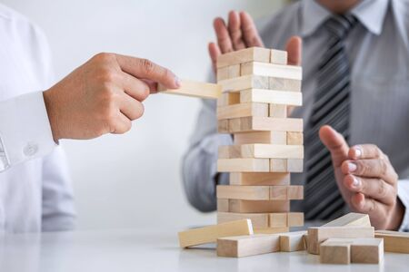 Planning Risk and Strategy in Business, Image of two Businessman hand placing making wooden block structure growing up the tower and protection to planning and development to successful.