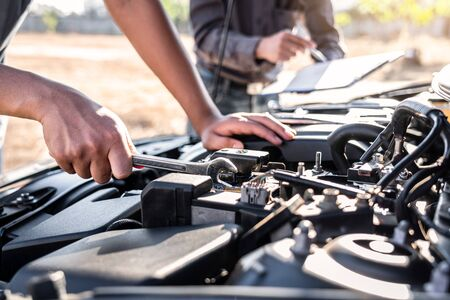 Technician team working of car mechanic in doing auto repair service and maintenance worker repairing vehicle with wrench, Service and Maintenance car check.