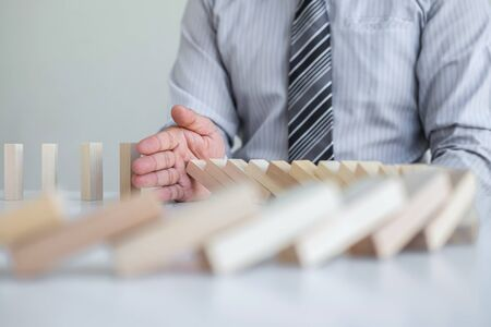 Planning Risk and Strategy in Business, Image of hand Businessman stopping and protection for collapse of wooden block game being falling down dominoes effect problem solving of prevent. Stock Photo