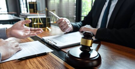 Male lawyer discussing negotiation legal case with client meeting with document contact in courtroom, law and justice concept.