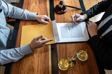Professional male lawyer or counselor discussing negotiation legal case with client meeting with document contract in office, law and justice, attorney, lawsuit concept. 版權商用圖片