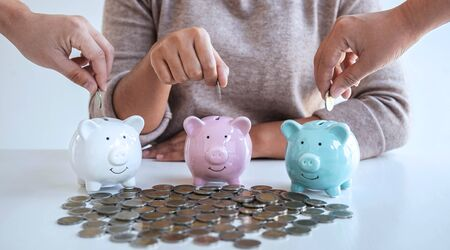 Image of hands putting coins into piggy bank planning growing saving to strategy with money box for future plan fund of travel, education, home and retirement.