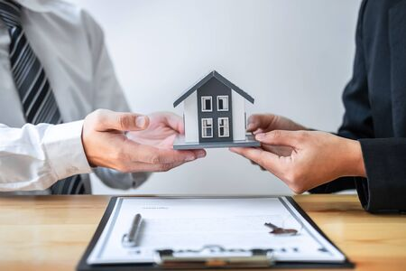 Estate agent are presenting home loan and giving house to client after discussing and signing agreement contract with approved application form, Home Insurance and Real estate investment concept.