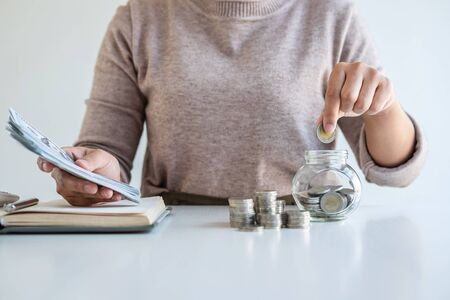 Young woman putting money into money box planning growing saving to strategy and calculation for future plan fund of travel, education, home and retirement.