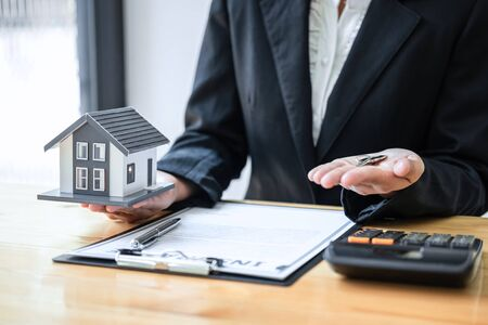 Real estate agent working sign agreement document contract for house insurance approving purchases for client with house model and key on table.
