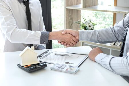 Real estate agent are shaking hands after good deal and giving house, keys to customer after signing contract to buy house with approved property application form.