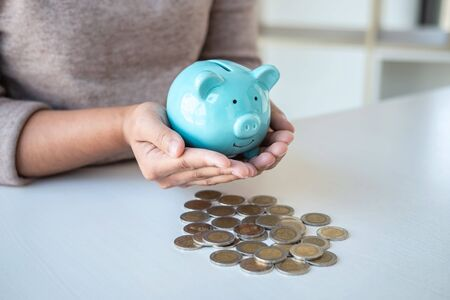 Young woman hands protection piggy bank and planning growing saving to strategy with pile coins for future plan fund of travel, education, home and retirement.
