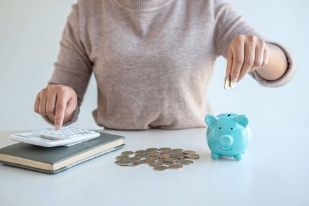 Young woman putting coins into piggy bank planning growing saving to strategy with money box for future plan fund of travel, education, home and retirement.