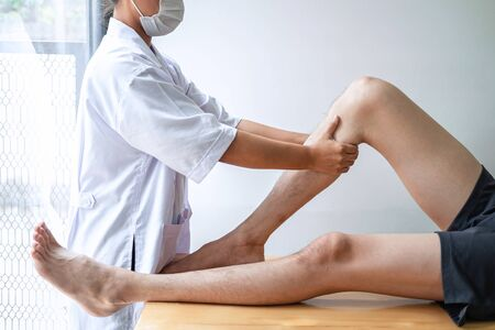 Female Physiotherapist working examining treating injured leg of male patient, Doing exercises the Rehabilitation therapy pain his in clinic.